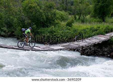 Biker on outboard bridge - stock photo