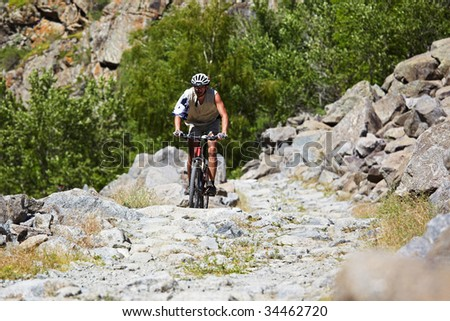 Biker on the old stone road in the rocky mountains - stock photo