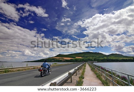 Biker on the road under amazing sky with nice clouds - summer - czech republic - stock photo