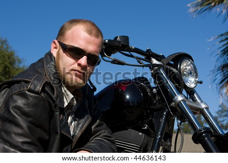 Biker poses in front of his motorcycle in black leather jacket with a serious look.
