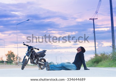 Biker relax sitting with motorbike on country road in sunset - stock photo
