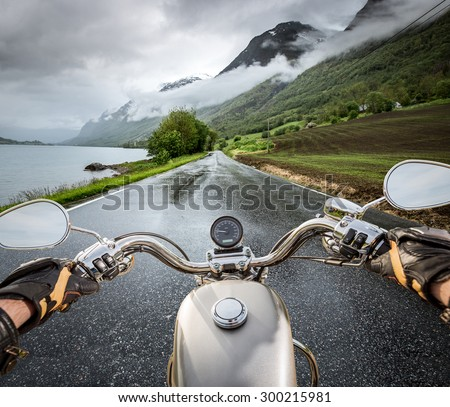 Biker rides a motorcycle in the rain. First-person view. - stock photo