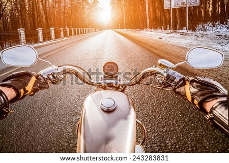 Biker rides on winter slippery road. First-person view. - stock photo