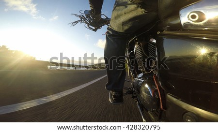 biker riding a classic motorcycle seen from the lift side - stock photo