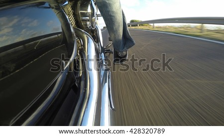 biker riding a classic motorcycle seen from the right side - stock photo