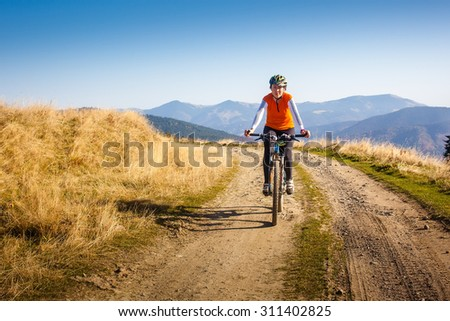 Biker riding in autumn mountains - stock photo