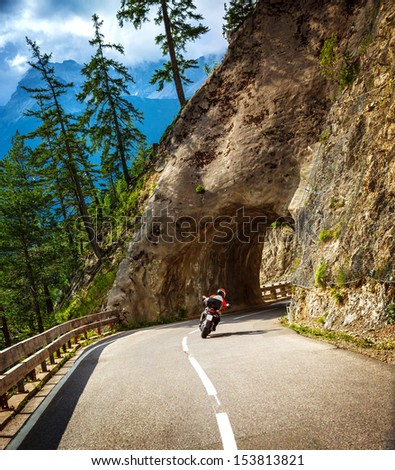 Biker riding into mountainous tunnel, extreme lifestyle, active holidays, race in Alps, Austria, Europe, moto sport, travel and tourism concept - stock photo