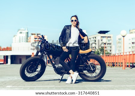 Biker sexy woman sitting on vintage custom motorcycle. Outdoor lifestyle toned portrait - stock photo
