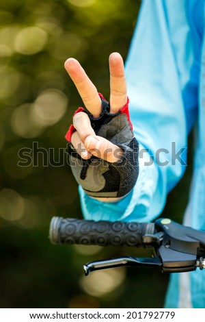 Biker showing victory sign - cycling concept image - stock photo