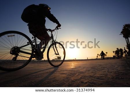 Biker silhouette riding along beach at sunset - stock photo