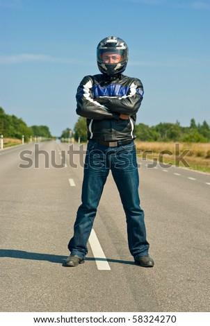 Biker standing in the center of empty road - stock photo