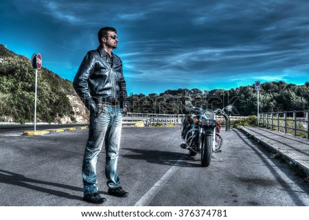 biker standing next to a classic motorcycle in hdr tone mapping effect