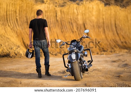 Biker standing with its motorbike on yellow sandy stone at sunset - stock photo