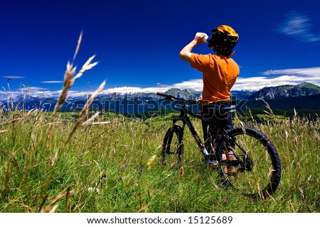Biker Stopped for drinking - in mountains on a sunny day (with plants over the sky at left)
