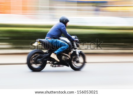 biker with a motorcycle in motion blur - stock photo