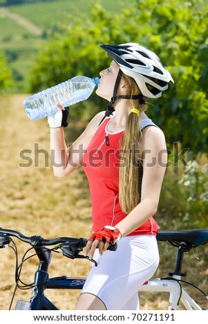 biker with bottle of water in vineyard - stock photo