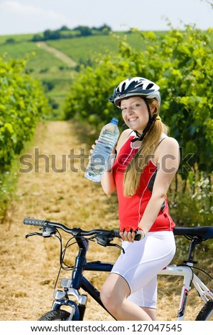 biker with bottle of water in vineyard, Czech Republic - stock photo