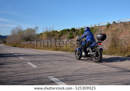 biker with helmet blue going by a road alone