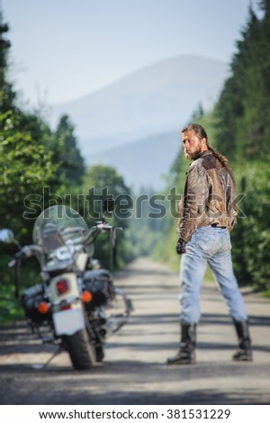 Biker with long hair wearing jacket blue jeans, boots and gloves standing near his custom made cruiser motorcycle on the open road. Looking to the camera. View from the back. Tilt shift soft effect - stock photo