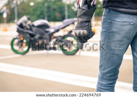 biker with motorcycle key. concept about transportation and motorbikes. - stock photo