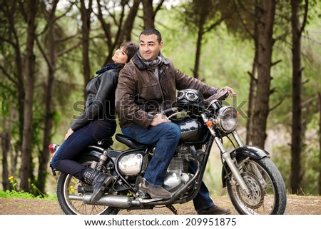 Bikers couple resting in the forest, two models posing on the motorcycle, active lifestyle, fashion style, romance and extreme concept - stock photo