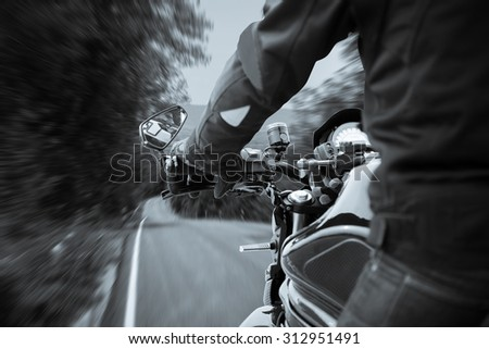 Bikers driving a motorcycle on misty asphalt road in selenium tone - stock photo