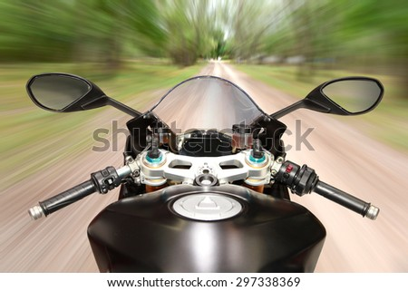 Bikers driving a motorcycle rides along the country road (blurred motion). - stock photo