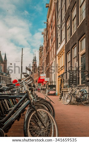 Bikes and Amsterdam - Amsterdam, The Netherlands - April 5, 2013: Bicycles parked at a street of this capital city in a typical Dutch urban scene. - stock photo