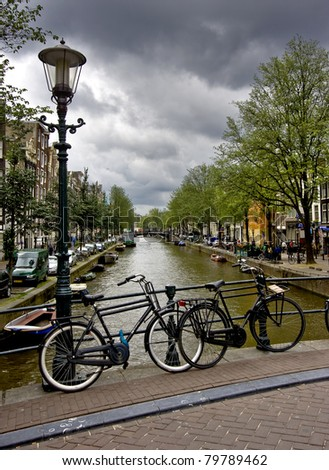 Bikes and lamppost in Amsterdam and canal - stock photo