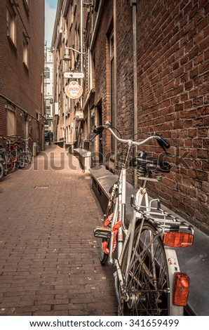 Bikes at an alley - Amsterdam, The Netherlands - April 5, 2013: Bicycles parked at a street of this capital city in a typical Dutch urban scene. - stock photo