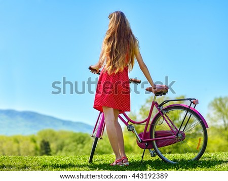 Bikes bicycle girl. Teenager girl wearing red polka dots dress looking into distance keeps bicycle with flowers basket. Green grass. Back view. - stock photo