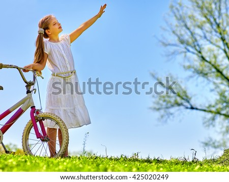 Bikes bicycling girl. Child girl wearing white skirt hand up and pleased near to bicycle. Girl looks away. Blue sky and green tree on background. Rural holiday. Summer park outdoor. - stock photo