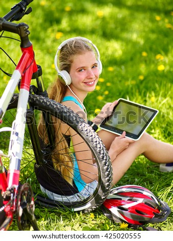 Bikes bicycling girl. Girl rides bicycle. Girl wearing headset in cycling keeps pc tablet and sitting near bicycle. Cyclist looking at camera. - stock photo
