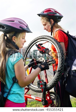Bikes bicyclist girl. Children girls wearing bicycle helmet with hand pump for bicycle. Girl pump up bicycle tire. Children bicycle repair. - stock photo