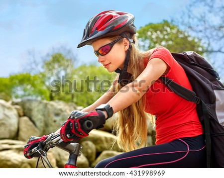 Bikes bicyclist girl. Girl wearing bicycle helmet and glass with rucksack ciclyng road bicycle. Looks down. - stock photo