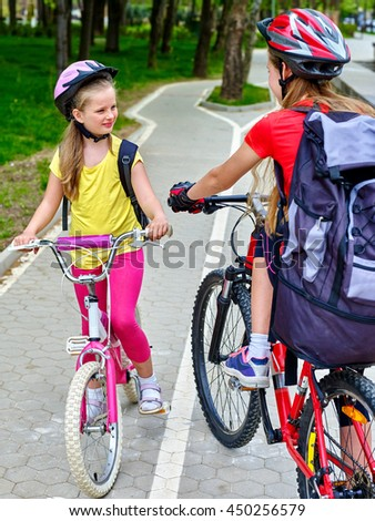 Bikes bicyclist girl. Girls wearing bicycle helmet and glass with rucksack ciclyng bicycle. Girls children cycling meet on white bike lane. - stock photo
