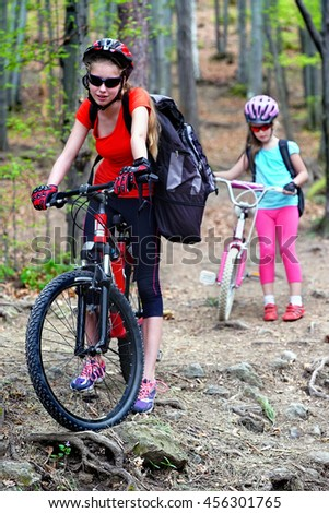 Bikes bicyclist girl. Girls wearing bicycle helmet and glasses with rucksack rides bicycle. Girls children are bicycling in summer park. Biking is good for health. - stock photo