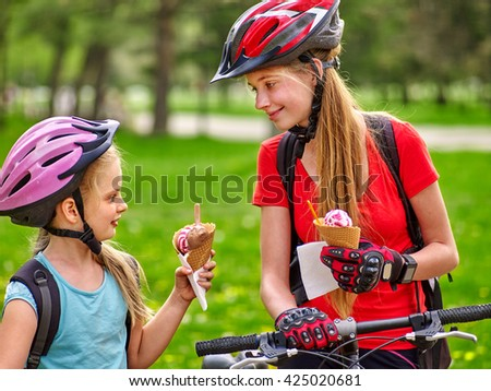 Bikes bicyclist girl. Girls wearing bicycle helmet and gloves with rucksack rides bicycle. Girls biking eating ice cream cone into summer park. Bicyclist is looking at each other. - stock photo