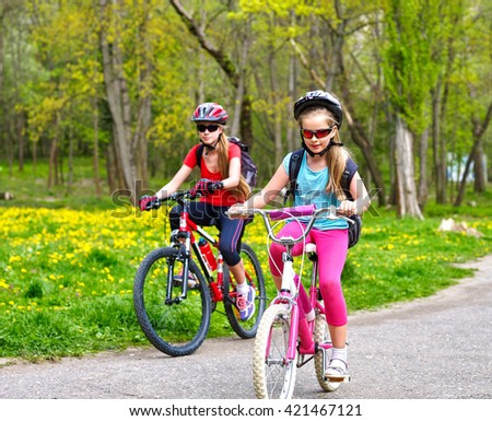 Bikes bicyclist girl. Girls wearing bicycle helmet  with rucksack ciclyng bicycle. Children outrace one another . Bike share program save money and time. Child in foreground  teenager on background. - stock photo