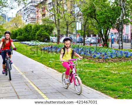 Bikes bicyclist girl. Girls wearing bicycle helmet  with rucksack ciclyng bicycle. Girls children cycling on yellow bike lane. Bike share program save money and time. Children outrace one another. - stock photo