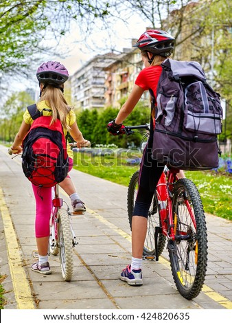 Bikes bicyclist girl. Girls wearing bicycle helmet with rucksack ciclyng bicycle. Girls children cycling on yellow bike lane. Bike share program save money and time at city street. Back view. - stock photo