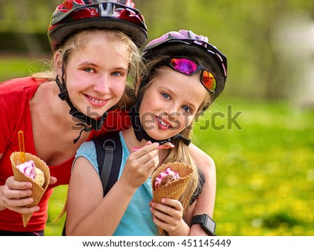 Bikes bicyclist girl. Girls wearing bicycle helmet with rucksack rides bicycle in summer park. Happy girls biking eating ice cream cone . Bicyclist is looking at camera. - stock photo