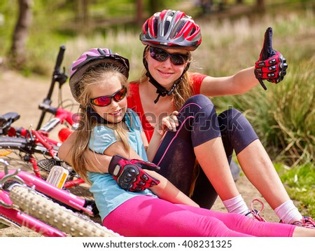 Bikes cycling family. Happy mother and daughter are sitting on road near bicycles.  - stock photo