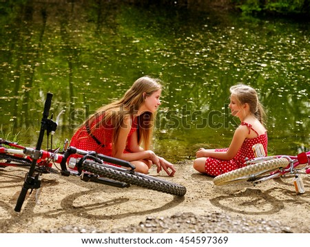 Bikes cycling family. Happy mother and daughter rides bicycle. Family have rest near water in park. Bicycles are on coast river into park. - stock photo