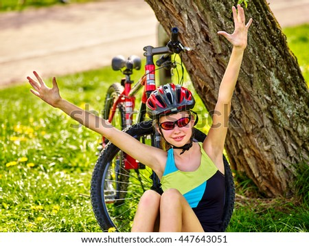 Bikes cycling girl. Girl rides bicycle. Girl in cycling sitting near bicycle and hand up. Cycling is good for health and mood. Cyclist looking into distance. - stock photo