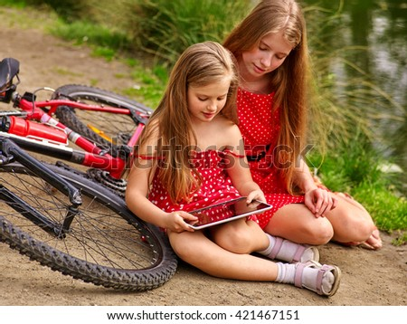 Bikes cycling girl. Two girls sisters  wearing red polka dots dress recreation near bicycle into park.  Children watch tablet pc. Girl in ecotourism. - stock photo