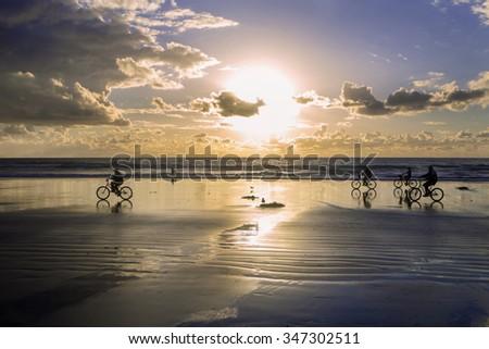 bikes on the beach at sunset - stock photo