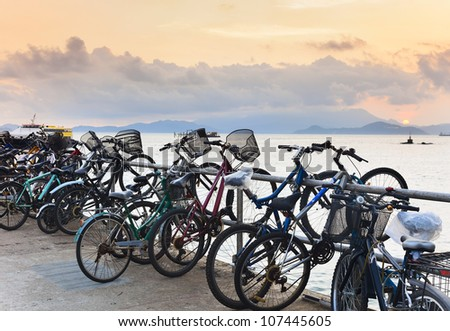 Bikes on the pier at sunset, which left residents of island, when sailing on ferry to mainland - stock photo