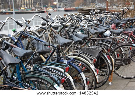 Bikes parked in a line along amsterdam canal.