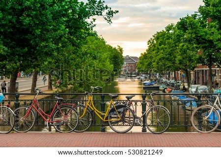 Bikes parked on a bridge in Amsterdam at sunset